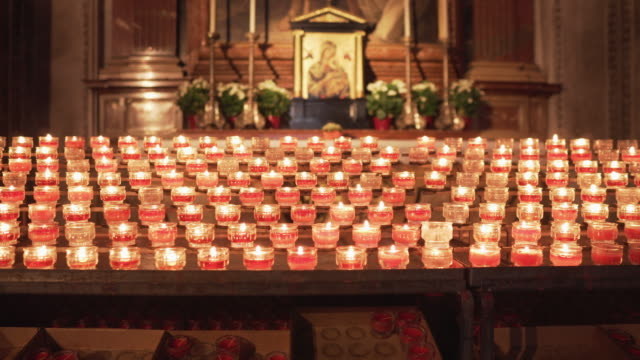 mary and the candles, red prayer candles burning in a row inside a catholic church for praying and spirituality, salzburg cathedral, the baroque cathedral of the roman catholic archdiocese of salzburg city, salzburg, austria. - cathedral stock videos & royalty-free footage