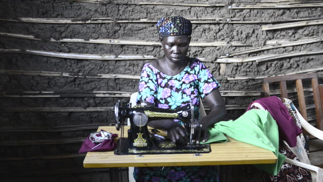 brac project, mary john, self supporting single mother with four kids who have gone or are going through brac sponsored school. brac trained her bought sewing machine for small business. makes about $200 a month. - ブラック島点の映像素材/bロール