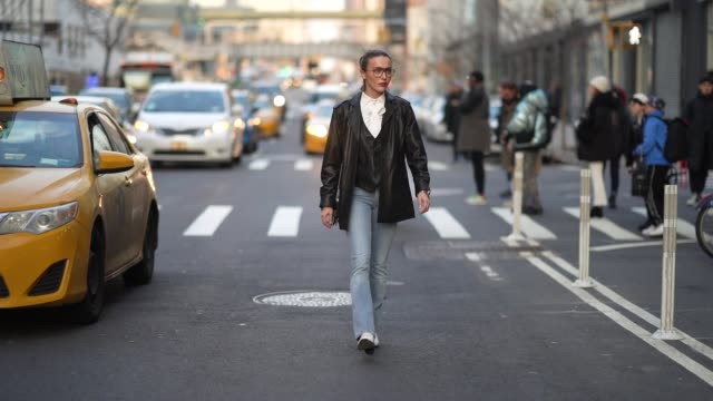 mary leest wears glasses, a white ruffled shirt, a black leather jacket, blue denim jeans, white shoes, outside zadig & voltaire, during new york... - ニューヨークファッションウィーク点の映像素材/bロール
