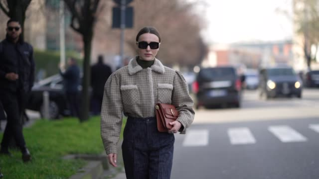 mary leest wears sunglasses, a green turtleneck top, an oversized jacket with large sleeves and white wool parts on the collar, a blue denim skirt, a... - fashion week stock videos & royalty-free footage
