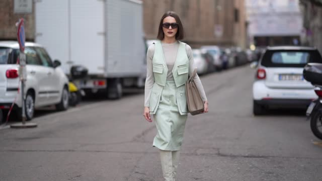 mary leest wears sunglasses, a pale green jacket, a gray top, a skirt, gray thigh high pointy boots, a brown leather bag, outside max mara, during... - gray jacket stock videos & royalty-free footage