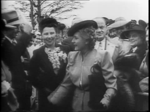 mary pickford walking between rows of fans, stopping to shake hands / she receives flowers from a little girl / pickford speaking with women war... - autographing stock videos & royalty-free footage