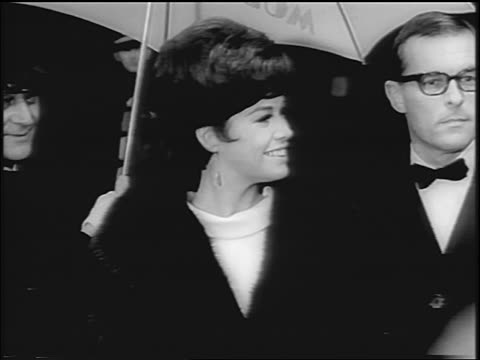 vídeos y material grabado en eventos de stock de mary tyler moore + husband, grant tinker standing under umbrella / she looks around smiling - pareja de mediana edad
