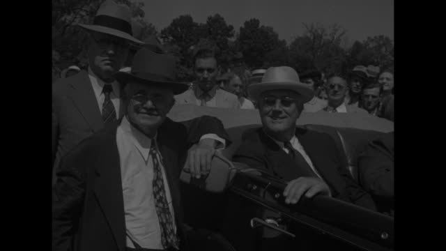 vidéos et rushes de president franklin roosevelt riding in open car moving down town street can see banner reading we want tydings crowd standing nearby / ms... - homme politique
