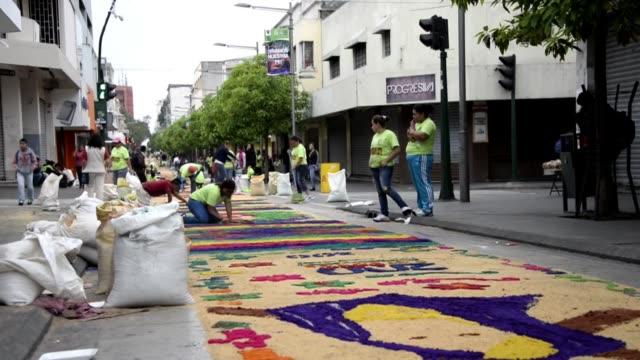 vídeos y material grabado en eventos de stock de mas de 6000 catolicos guatemaltecos la mayoria jovenes voluntarios elaboraron este jueves santo una alfombra de aserrin de 2300 m de largo en el... - jueves