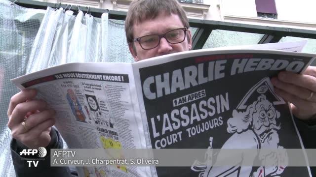 vídeos de stock, filmes e b-roll de mas satirico que nunca charlie hebdo pone en portada un dios con la leyenda el asesino sigue suelto la vispera del aniversario del ataque que diezmo... - sátira