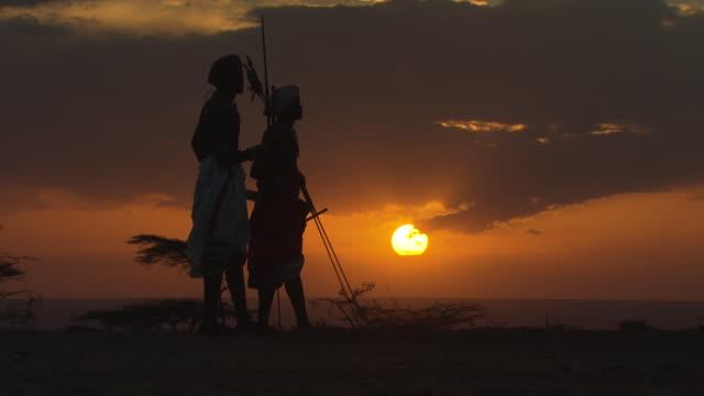 masai and samburu warriors standing silhouetted by sunset, kenya - krieger menschliche tätigkeit stock-videos und b-roll-filmmaterial