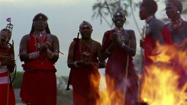vídeos de stock e filmes b-roll de ms pan masai tribal dance with people clapping + fire in foreground / kenya - cultura indígena