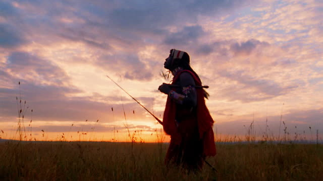 MS Masai tribesman performs traditional jumping on plain with sunset in background / Kenya
