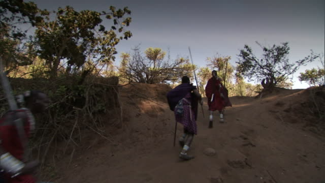 masai warriors carry spears as they hurry along a dirt path. - warrior person stock videos & royalty-free footage