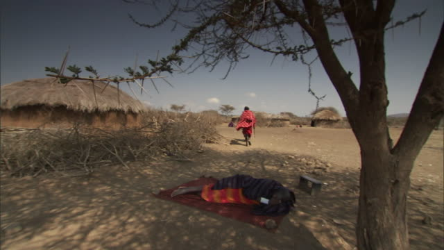 a masai woman rests on a blanket in the shade of a tree. - minority groups stock videos & royalty-free footage