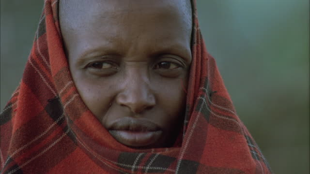 a masai woman wears a tartan pattern shawl. available in hd. - shawl stock videos and b-roll footage