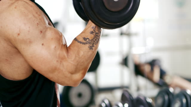 slo mo masculine man lifting dumbbells - dumbbell stock videos & royalty-free footage