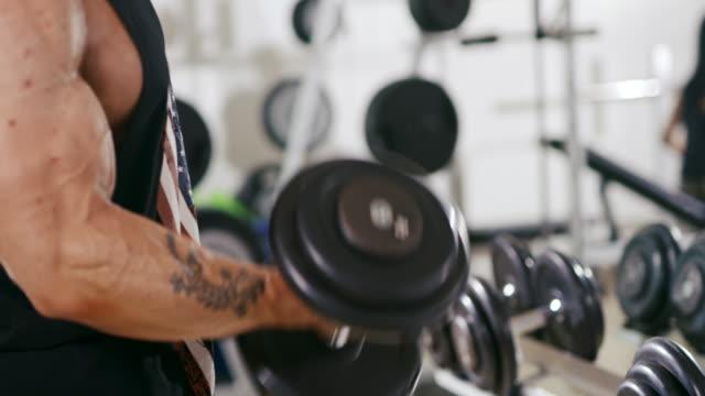 stockvideo's en b-roll-footage met slo mo mannelijke man tillen van zware dumbbells in de sportschool - menselijke arm