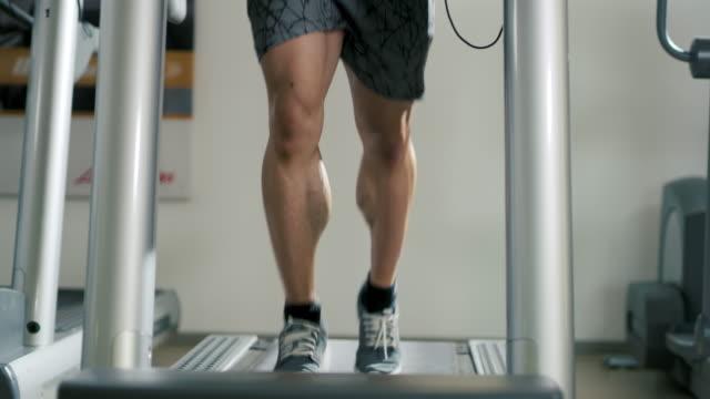 slo mo masculine man running on a treadmill - treadmill stock videos & royalty-free footage
