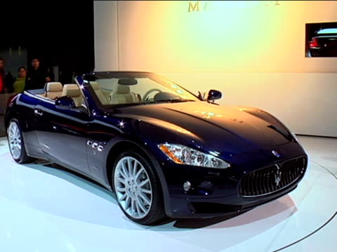 cu maserati sign on wall zo to ws maserati granturismo convertible revolving on turntable / cu floor sign tilt up to car on turntablefootage is 43... - anamorphic stock-videos und b-roll-filmmaterial
