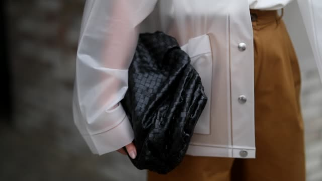 stockvideo's en b-roll-footage met masha sedgwick is seen wearing see through sheer proenza schouler rain jacket beige brown pants bally white tshirt calvin klein black clutch bottega... - oorbel