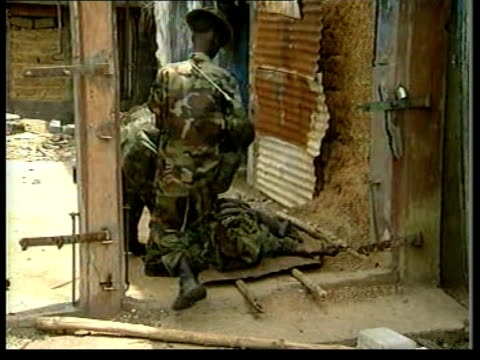 masiaka ext la burnt out car next to burnt out shell of house gv rubble next to hole in wall of building armed progovernment soldiers along side... - rocket launcher stock videos & royalty-free footage
