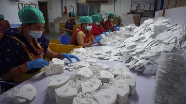 mask factory on the outskirt of ahmedabad in gujarat is working 24/7 to meet the demand of face mask but is worried about access to raw materials as... - protective workwear stock-videos und b-roll-filmmaterial