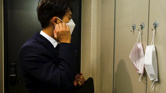mask in daily life - businessman coming back home with protective face mask at front door - homecoming stock videos & royalty-free footage