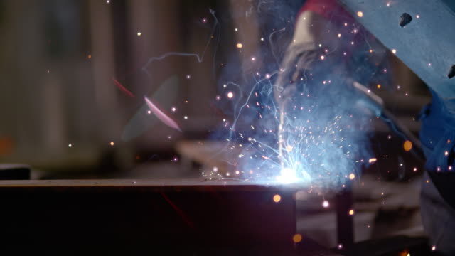 slo mo pan mask protecting worker from welding sparks - stahl stock-videos und b-roll-filmmaterial