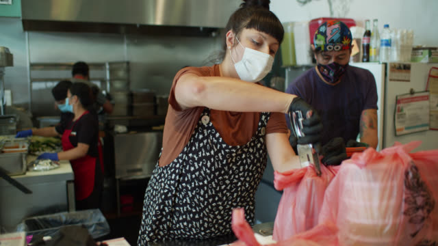 masked and gloved restaurant staff wearing at work assembling take out and delivery orders during covid-19 lockdown - taco stand stock videos & royalty-free footage