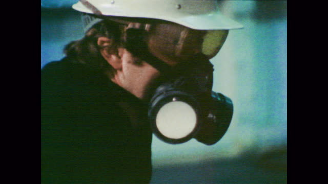 1978 Masked and unmasked commercial painters work as doctor voiceover explains increased risk of lung cancer in painters