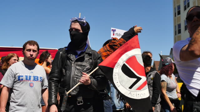 a masked antifa protester holds an antifa flag near alamo square in san francisco california where protesters gathered after members of patriot... - anti fascism stock videos & royalty-free footage