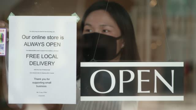 stockvideo's en b-roll-footage met gemaskerde aziatische winkeleigenaar die haar opslag opent en een sociaal het distantiëren bericht op de deur plaatst - heropening