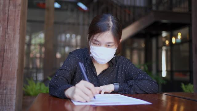 vídeos de stock, filmes e b-roll de mulher asiática mascarada tique-taque e assinando sua cédula de votação após chegar a uma decisão - política