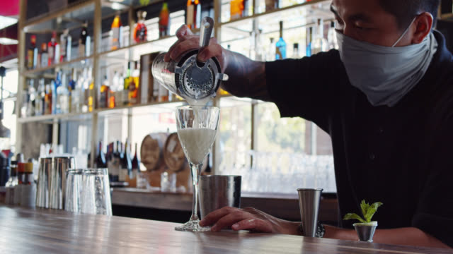 Masked Bartender Pouring Drink Into Glass at Socially Distanced Bar
