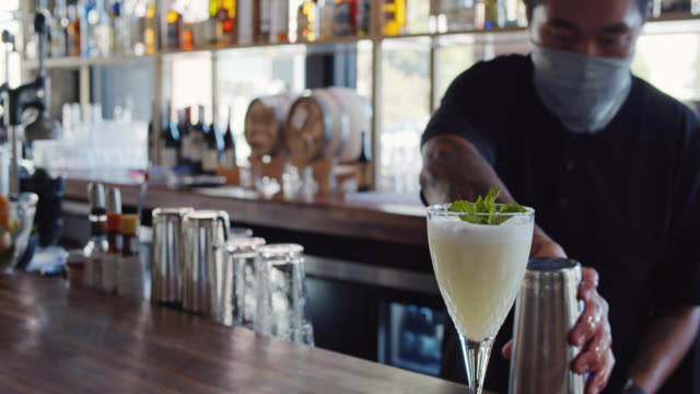 Masked Bartender Working Behind Bar at Establishment Practicing Social Distancing