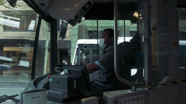 a masked bus driver closes the bus doors during morning peak hour at wynyard bus station sydney cbd on march 31 2020 in sydney australia public... - bus driver stock videos & royalty-free footage