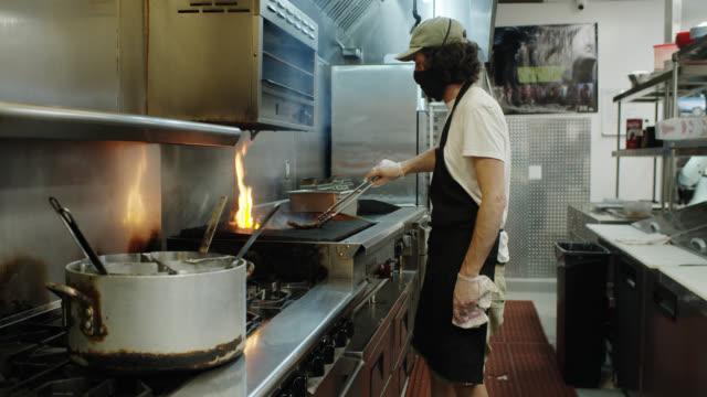 vídeos de stock e filmes b-roll de masked chef grilling food for takeout during covid-19 outbreak - serviços essenciais