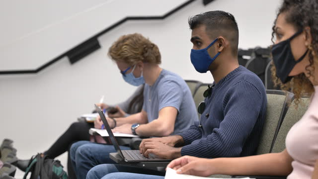 masked college students in a lecture hall - lockdown stock videos & royalty-free footage