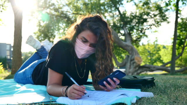 masked female student studying under a tree on campus - spanish and portuguese ethnicity stock videos & royalty-free footage