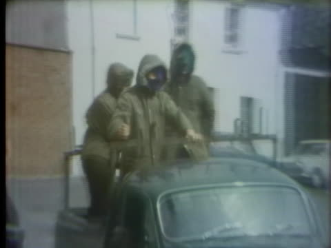 masked ira members watch from the back of a pickup as a bulldozer removes debris. - irlanda del nord video stock e b–roll