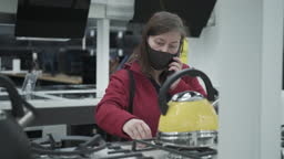 Masked lady picks out a new stove in home appliance shop