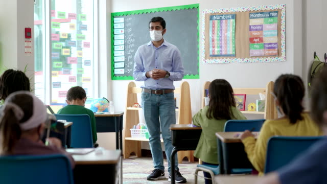 masked male teacher speaking to students in class - teacher stock videos & royalty-free footage