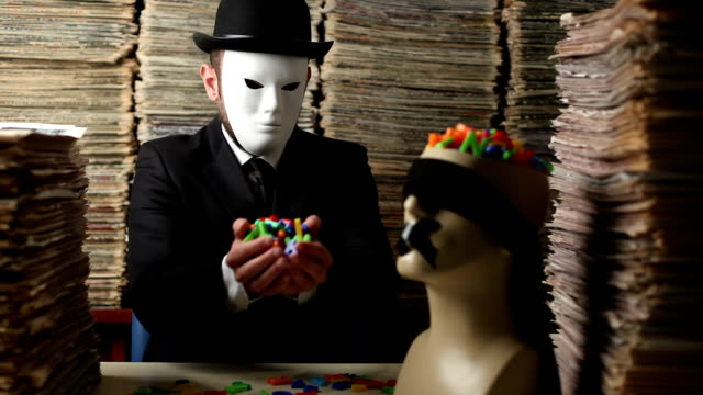 Masked Man Filling Mannequin Head With Letters For Censorship Concept