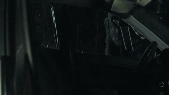 vídeos de stock, filmes e b-roll de homem mascarado tentando roubar o carro no meio da noite - à prova de balas