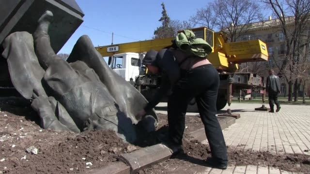 masked men smashed communist era monuments in ukraine's second cityafter the country's pro western parliament voted to purge the nation of soviet... - comunismo video stock e b–roll