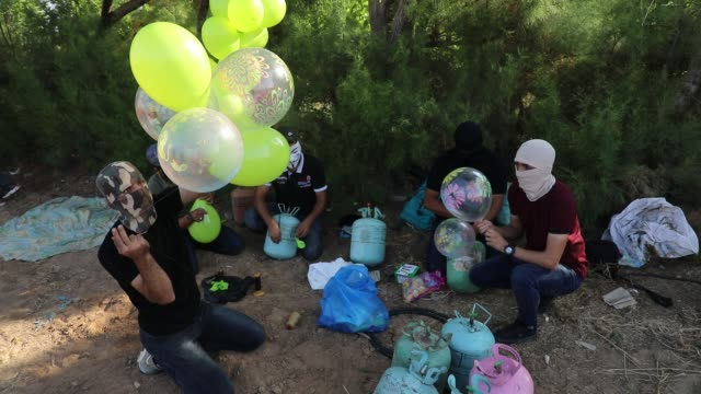 masked palestinians attach incendiary devices to balloons before releasing them towards israeli lands in the northern gaza strip, along the... - gaza strip stock videos & royalty-free footage