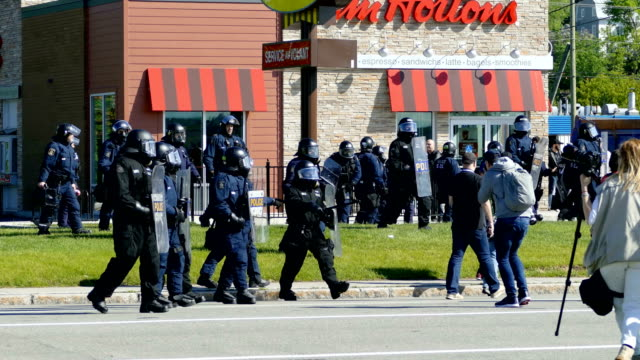 cu masked protestors / riot police move into position past a tim horton's and other shops - centro commerciale suburbano video stock e b–roll