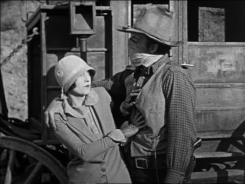 B/W 1924 masked robber putting arms around woman in stagecoach hold-up / feature