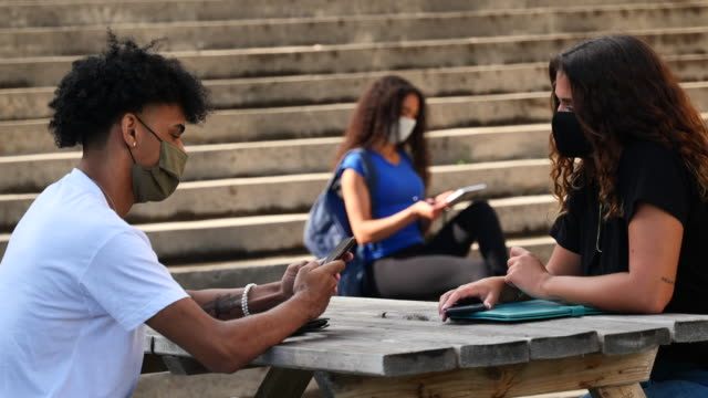 masked students of different ethnicities studying outside on campus - back to school stock videos & royalty-free footage