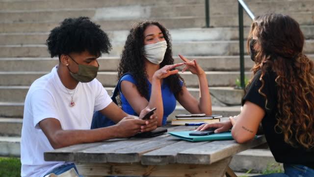 vidéos et rushes de étudiants masqués de différentes ethnies étudiant à l'extérieur sur le campus - étudiant