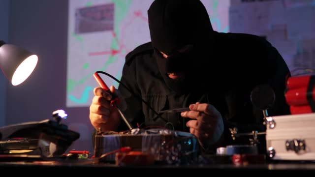masked terrorist constructing a bomb in workshop - home made stock videos & royalty-free footage