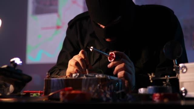 vídeos y material grabado en eventos de stock de terrorista enmascarado construyendo una bomba - haz de luz