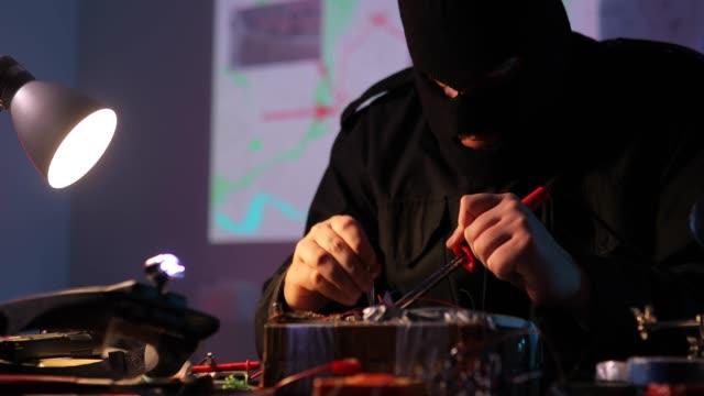 vídeos y material grabado en eventos de stock de terrorista enmascarado construyendo una bomba de tiempo en el taller - haz de luz
